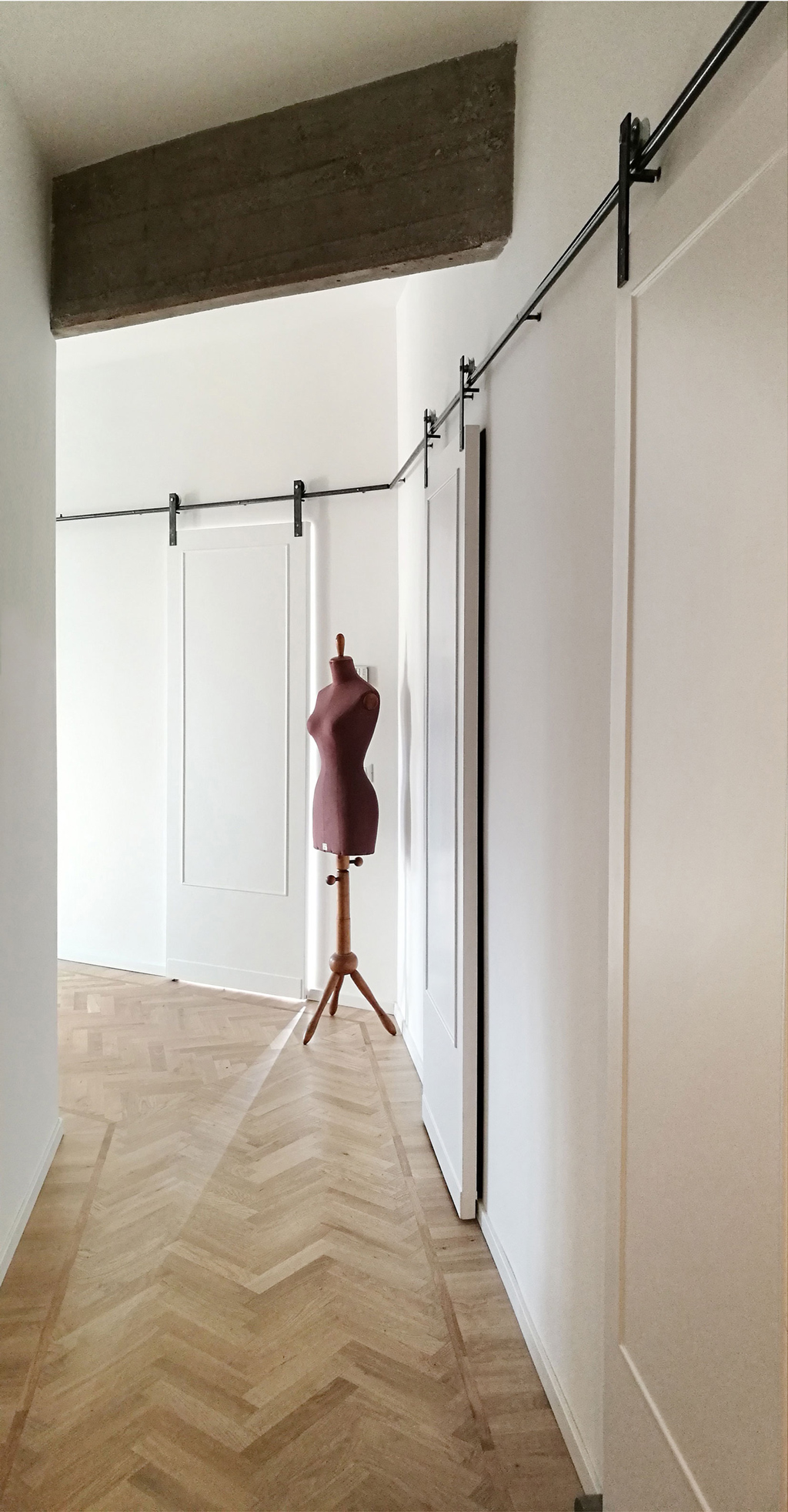 corridor entrance with white sliding panel doors and clothes dummy