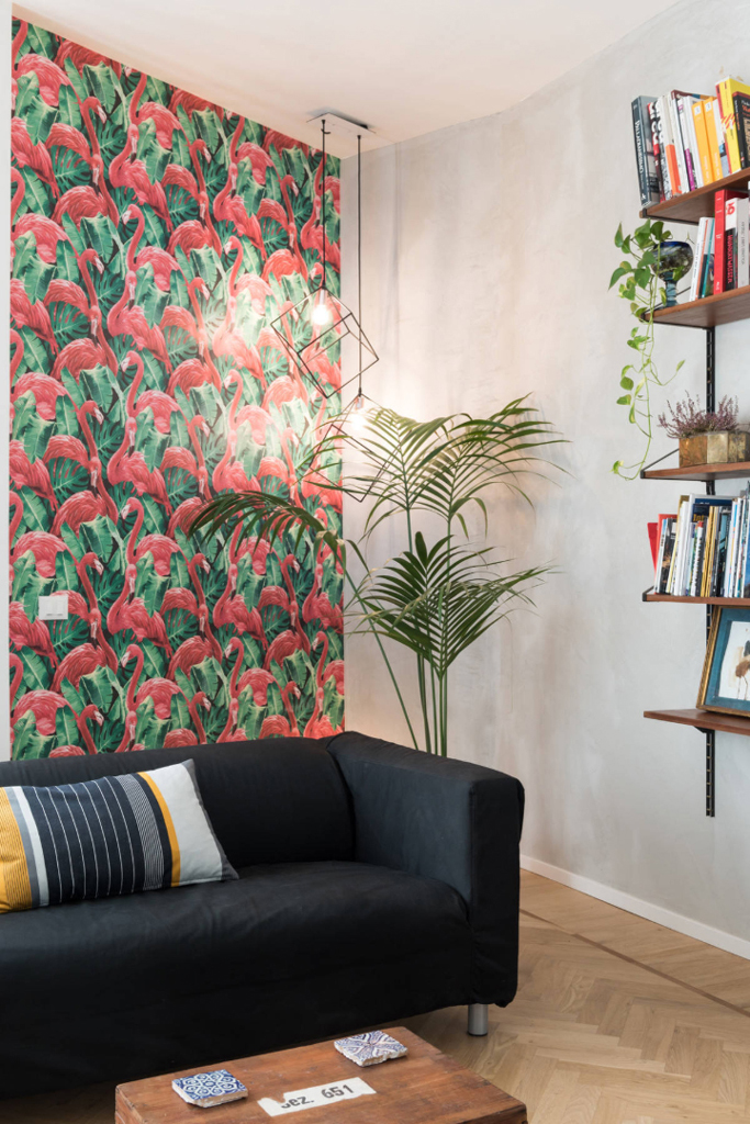 livingroom decorated with wallpaper flamingos a Kentia plant and a concrete wall