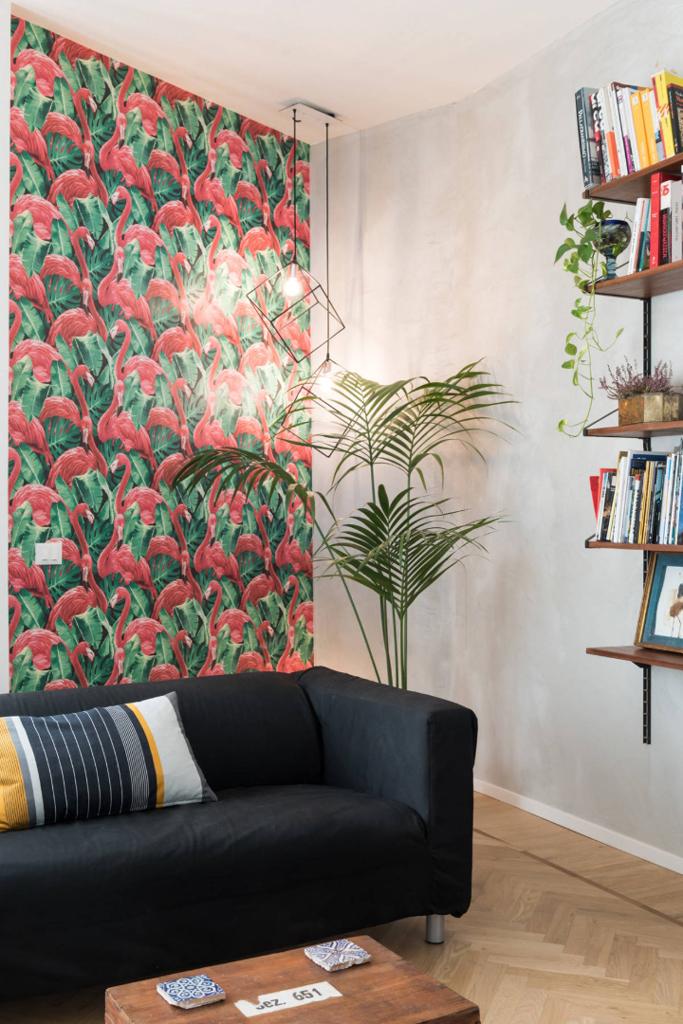 salon décoré de flamants roses de papier peint une plante De Kentia et un mur de béton